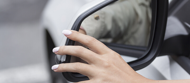 woman adjusting exterior car mirror